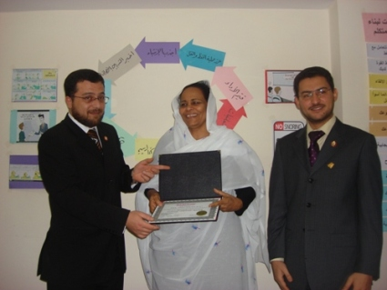 Trainee Amaal Abdelmajeed is receiving her certificate from the trainers Mohammad Pedra and trainer Tony Peter