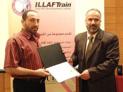 الاستاذ  عبد الله وهو يستلم شهادة التخرج من الدكتور رائد الذهبي