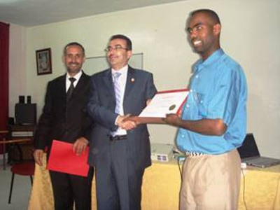 Trainer Ahmad Alkhateeb is handing a certificate to trainee Khalid Fakhri