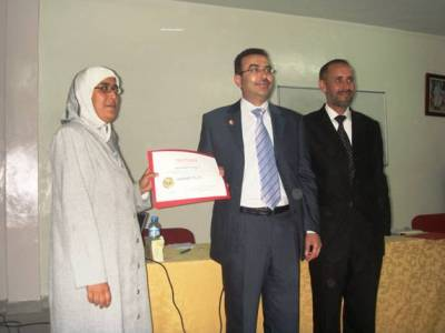 Trainee Rachida Sahli is receiving her certificate from trainer Alkhateeb