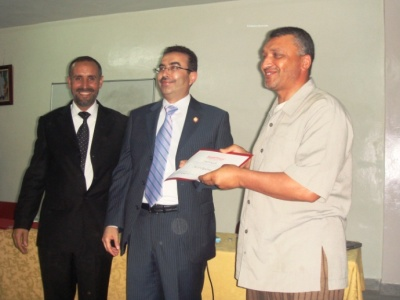 Trainer Ahmad Naser Alkhateeb is handing a certificate to Trainee Idriss Jodar with the attendance of Mr. Ibrahim Talioua