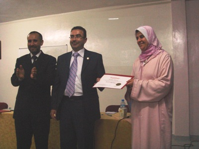 Trainer Ahmad Naser Alkhateeb is handing a certificate to trainee Latifa Elboustani