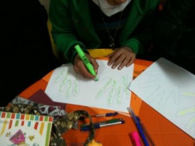 المتدربون يكتبون أهدافهم ومعيقاتها على صور لكف أيديهم.