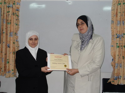 Trainee Hanan Mathbout while receiving the certificate from the trainer