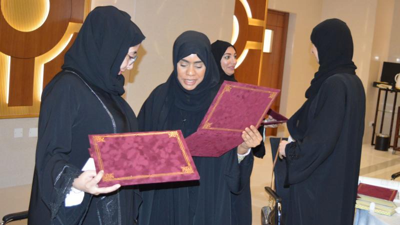 المشاركون أثناء تسليم بعضهم البعض الشهادات
