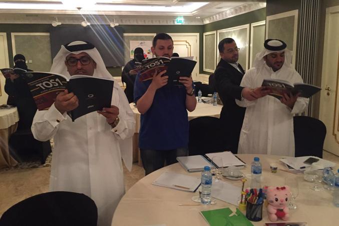 المتدربون وتنفيذ تمرين من خلال القراءة في كتاب TOS1